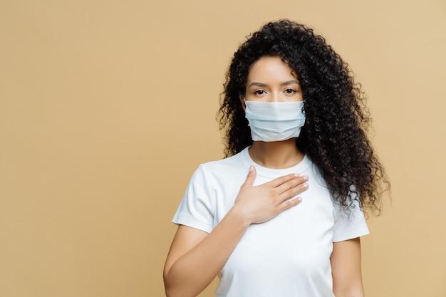 Mulher afro-americana séria usa máscara médica, tem problemas respiratórios, pressiona a mão no peito, foi infectada com coronavírus Foto Premium