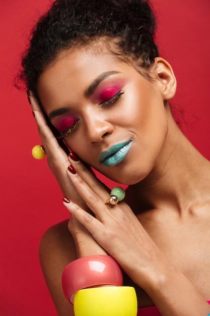 Mulher afro-americana sorridente com maquiagem colorida brilhante, colocando a cabeça na palma da mão, isolada sobre parede vermelha Foto gratuita