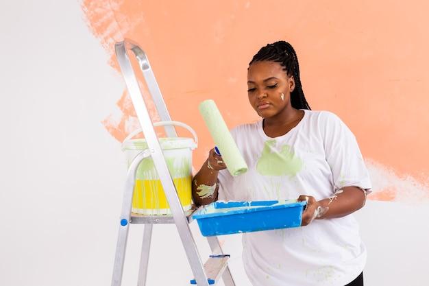Mulher afro-americana sorridente, pintando a parede interior da casa. renovação, reparo e redecoração Foto Premium