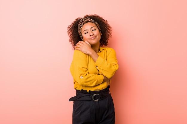 Mulher afro-americano nova contra abraços cor-de-rosa, sorrindo despreocupado e feliz. Foto Premium
