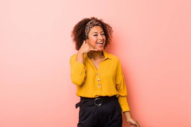 Mulher afro-americano nova no rosa que mostra um gesto de chamada de telefone móvel com dedos. Foto Premium
