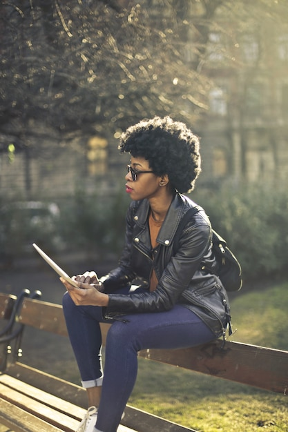 Mulher afro elegante em um parque com um tablet Foto Premium