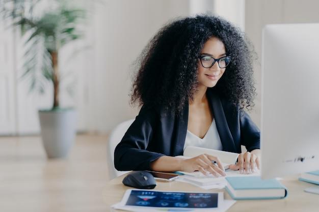 Mulher afro freelancer trabalha remotamente, escreve informações, focada na tela do computador com expressão encantada Foto Premium