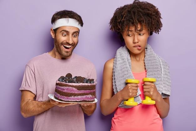 Mulher afro infeliz tenta sua força de vontade, morde os lábios ao olhar para um saboroso bolo assado nas mãos do homem, faz dieta, trabalha para perder peso, fica de pé com halteres e toalha no pescoço. esporte, nutrição Foto gratuita