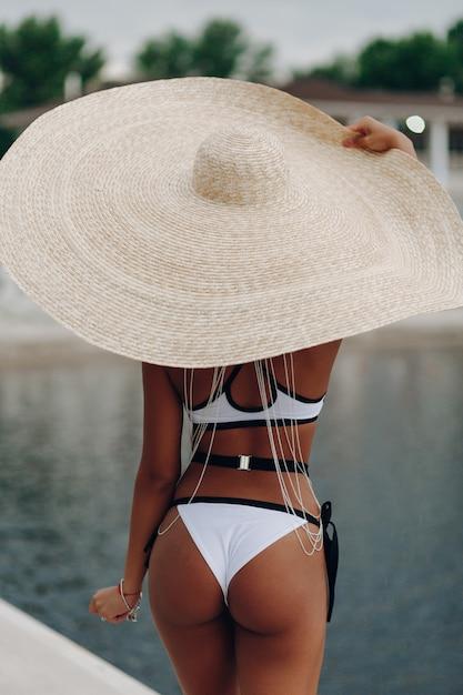 Mulher afro nova bonita no biquini que relaxa perto da piscina que veste o chapéu de palha grande. Foto gratuita