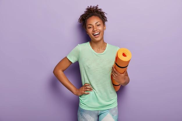 Mulher afro positiva em forma física faz exercícios físicos e malha em casa, segura karemat laranja Foto gratuita