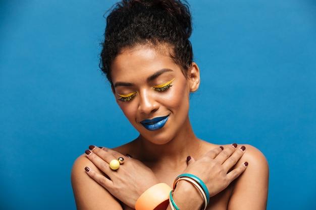 Mulher afro sorridente relaxada com maquiagem extravagante e acessórios posando com os olhos fechados e cruzou as mãos no peito, parede azul Foto gratuita