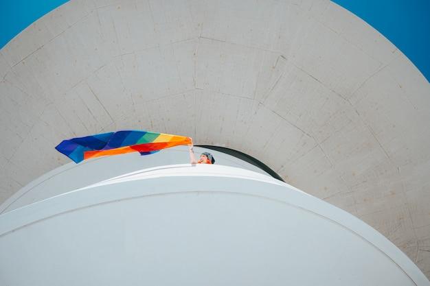 Mulher agitando a bandeira do orgulho gay do topo de um prédio Foto Premium