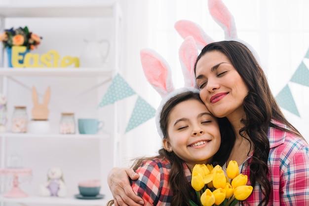 Mulher agradável e sua filha, abraçando uns aos outros no dia de páscoa Foto gratuita