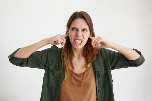 Mulher agressiva, tampando os ouvidos, ficando com raiva de barulho. jovem irritada tentando evitar sons altos Foto gratuita