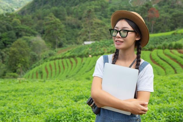 Mulher agrícola que inspeciona a planta com comprimidos de criação - um conceito moderno Foto gratuita