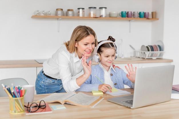 Mulher ajudando a filha a estudar em casa Foto Premium