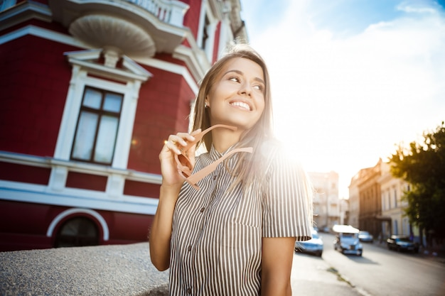 Mulher alegre bonita jovem em óculos de sol andando pela cidade, sorrindo. Foto gratuita