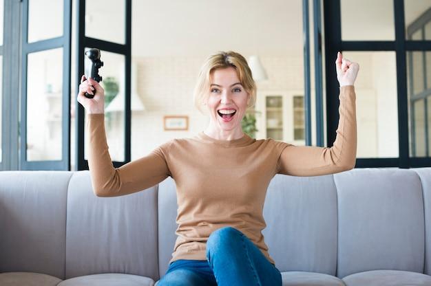 Mulher alegre com joystick no sofá Foto gratuita