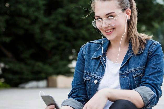 Mulher alegre com smartphone sentado na calçada Foto gratuita