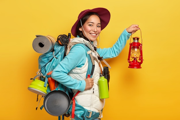 Mulher alegre de trekker segura lâmpada de querosene, usa chapéu e roupa casual, vai descansar na floresta e carrega mochila Foto gratuita