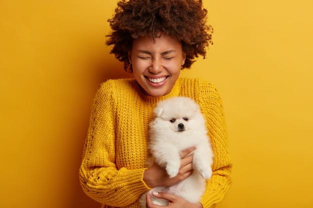 Mulher alegre e cacheada com spitz branco fofo leva cachorro para o salão de beleza, feliz por receber o animal de estimação da raça favorita como presente do namorado Foto gratuita
