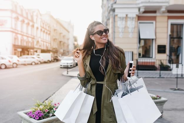 Mulher alegre em óculos de sol elegantes passando um tempo na cidade comprando roupas novas Foto gratuita