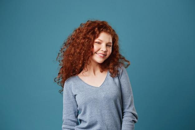 Mulher alegre jovem estudante com cabelos ondulados vermelhos e sardas sorrindo brilhantemente mostrando os dentes, posando para o álbum de fotos de formatura. Foto gratuita