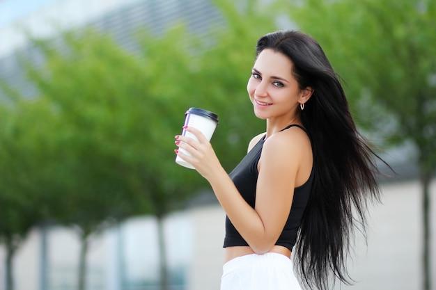 Mulher alegre na rua bebendo café da manhã no sol Foto Premium