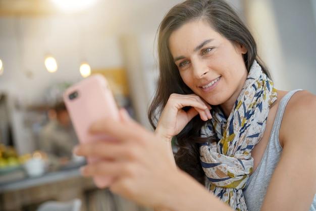 Mulher alegre no café usando smartphone para chamada de vídeo Foto Premium