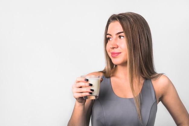 Mulher alegre nova atrativa no sportswear com vidro do leite Foto gratuita