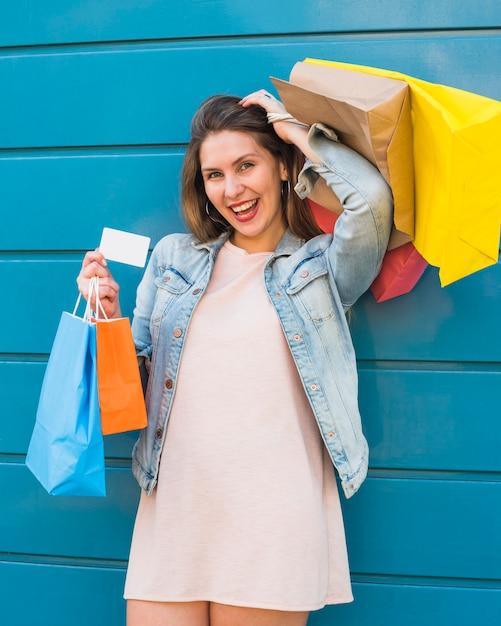 Mulher alegre permanente com sacos de compras e cartão de crédito Foto gratuita