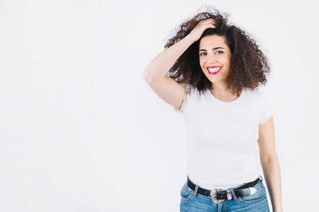 Mulher alegre que ajusta o cabelo Foto gratuita