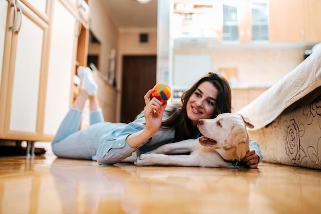 Mulher alegre que joga com seu cão no apartamento. Foto Premium