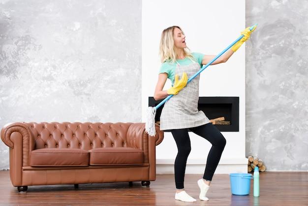 Mulher alegre que joga o espanador como a guitarra que está na casa perto do sofá Foto gratuita