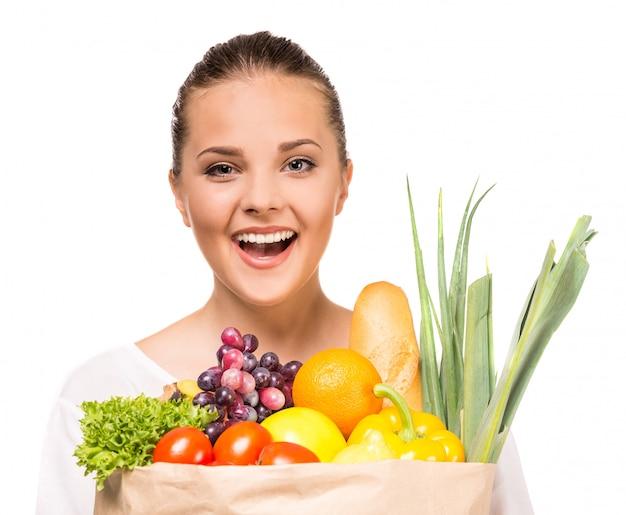 Mulher alegre que mantém o saco de compras completo dos alimentos frescos. Foto Premium