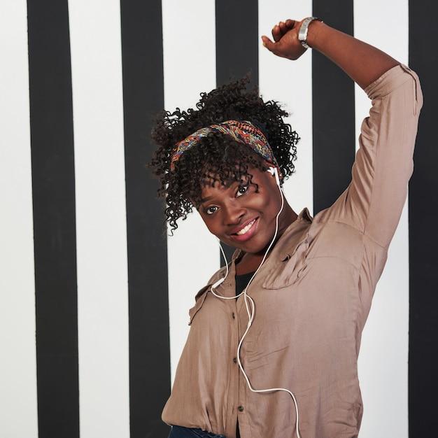 Mulher alegre sorriu garota afro-americana fica no estúdio com linhas verticais de brancas e pretas no fundo Foto gratuita