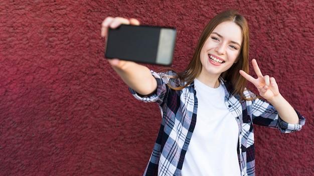 Mulher alegre tomando selfie com sinal de paz no pano de fundo texturizado parede áspera Foto gratuita