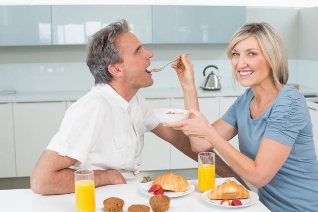 Mulher alimentando o homem na mesa de café da manhã na cozinha Foto Premium