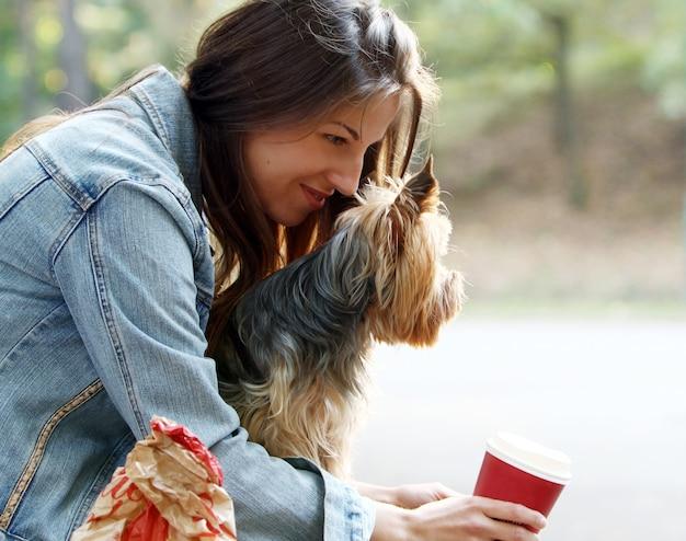 Mulher almoçar enquanto passeava com seu cachorro Foto gratuita