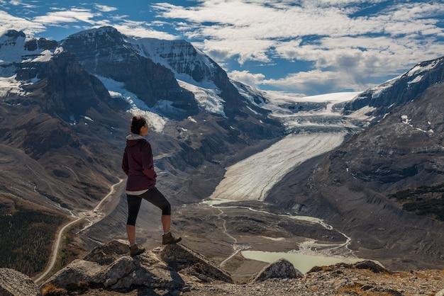 Mulher alpinista em pé no pico wilcox, olhando para os campos de gelo de columbia e a geleira athabasca, em jasper, alberta, canadá Foto Premium