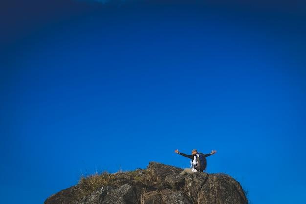 Mulher alpinista no penhasco de pedra contra o céu azul claro e nuvens Foto Premium