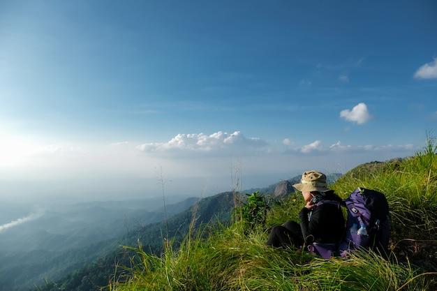Mulher alpinista sentado na grama verde no penhasco da montanha Foto Premium
