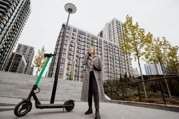 Mulher alugada scooter. outono na cidade grande. mulher atraente com roupas casuais discute os termos de aluguel de scooter de seu smartphone. blocos de apartamentos em segundo plano. scooters elétricos para compartilhamento público. Foto Premium