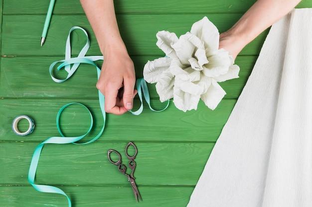 Mulher, amarrando, papel, flor, com, fita, contra, tabela madeira Foto gratuita