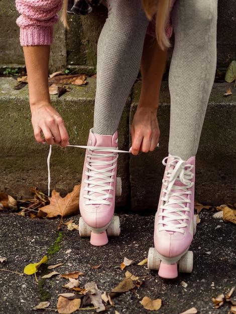 Mulher amarrar cadarços de patins Foto gratuita