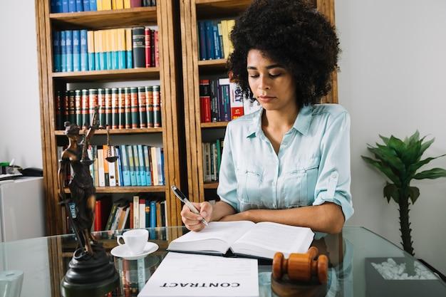 Mulher americana africana, escrita, em, livro, em, tabela, em, escritório Foto gratuita