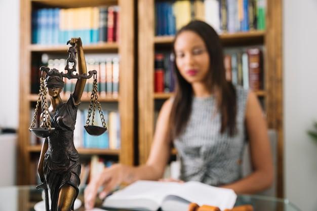 Mulher americana africana, livro leitura, tabela, com, estátua, em, escritório Foto gratuita