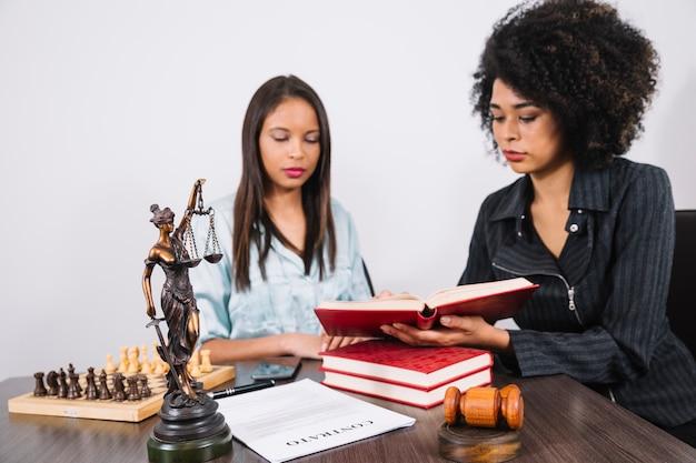 Mulher americana africana, mostrando, livro, para, senhora, tabela, com, documento, smartphone, e, xadrez Foto gratuita