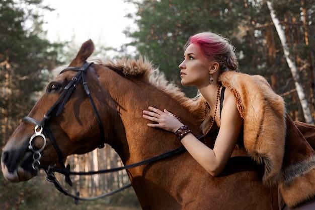 Mulher andando com outono de cavalo na natureza. rosto de mulher criativa maquiagem rosa quente, coloração de cabelo. retrato de uma mulher com um cavalo. passeios a cavalo na floresta de outono Foto Premium