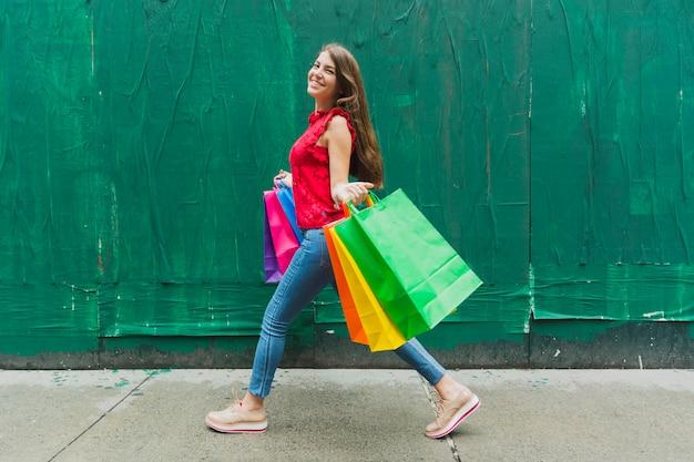 Mulher andando com sacolas de compras no fundo da parede verde Foto gratuita