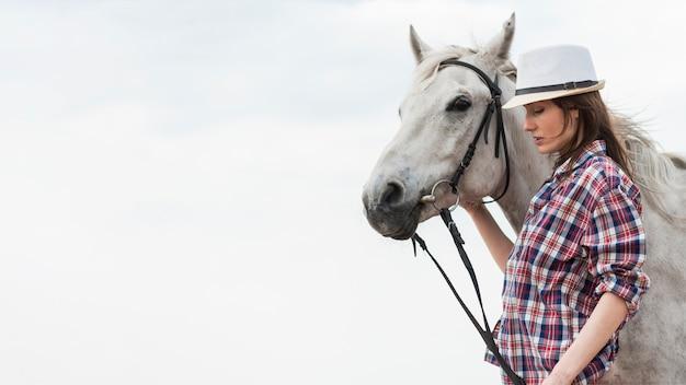 Mulher andando com um cavalo na praia Foto gratuita
