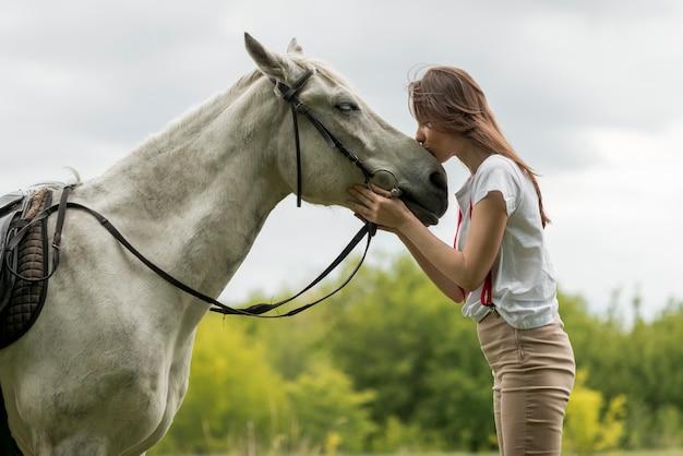 Mulher andando com um cavalo na zona rural Foto gratuita