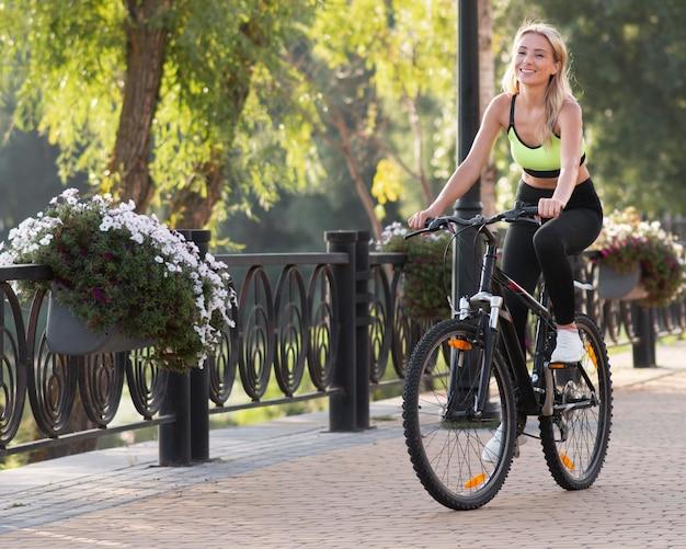 Mulher andando de bicicleta cercada pela natureza Foto Premium
