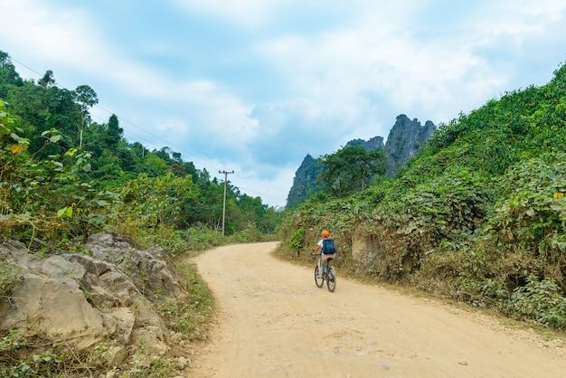Mulher andando de bicicleta de montanha na estrada de terra na paisagem cênica em torno de vang vieng mochileiros destino de viagem no laos Foto Premium